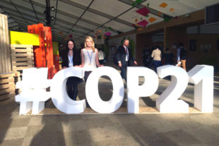 students behind large 3-D letters of #COP21