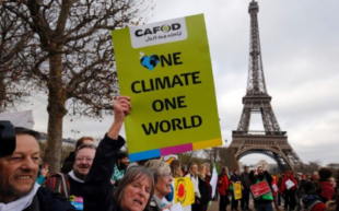 Crowd in Paris holding One Climate One World protest sign