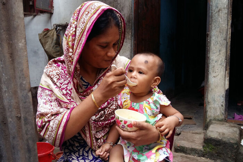 a mother feeds her child one of the therapeutic foods as part of the clinical trial.